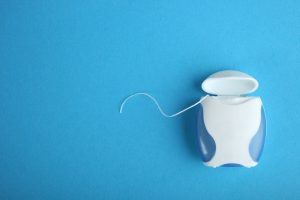 white floss container sitting on a blue background with some floss pulled out
